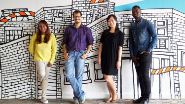Four international students lean against a wall.
