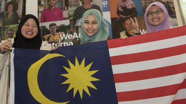 Malaysian students hold a flag.