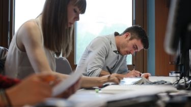 Postgraduate students writing and concentrating