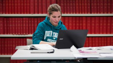Girl sat with laptop in library