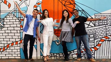 Four international students strike fun poses in front of mural