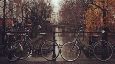 Two bikes near a river in Holland.