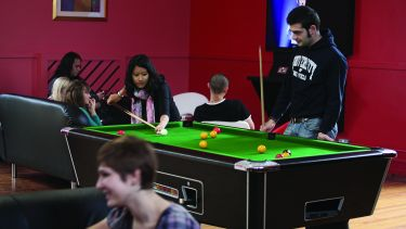 Students in accommodation playing pool.