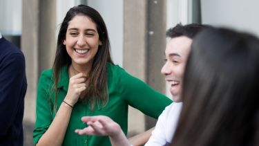 Photo of student laughing with group of friends