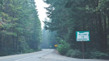 A welcome to oregon sign along a road in a wooded area