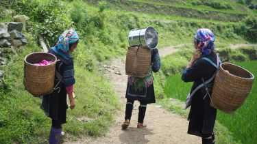 photo of three women carrying baskets on a hill path