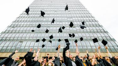 Graduates throwing hats outside Arts Tower