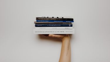 hand holding pile of books
