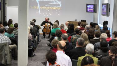 Cellist performing and talking at a seminar
