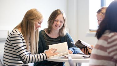Postgraduate students reading together in the common room