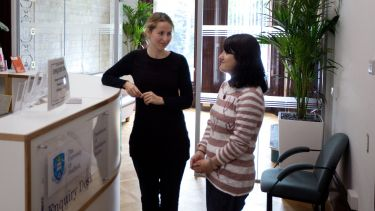 Two research students stood at the enquiry desk in the Department of Sociological Studies