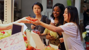 Three international students at food market