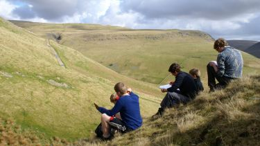 Geograpghy students sat on a hill during a fieldtrip taking notes - image