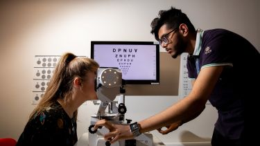 Research students in Orthoptics using equipment.