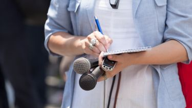 A journalist is taking notes while holding microphones