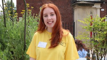 Megan Wood, English Language and Linguistics student, smiling at camera and wearing a yellow t shirt