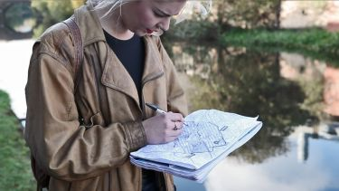 A student marking information on a map - image