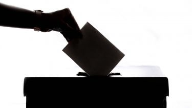 A person dropping a ballot paper into a box.