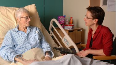 A researcher talking to a patient