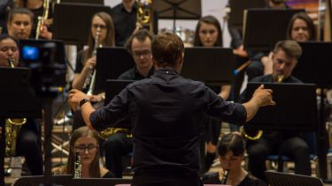 Man conducting Sheffield university wind orchestra