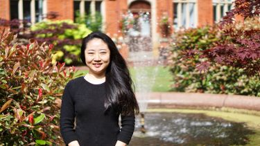 A chinese student infront of the fountains in Firth Court
