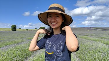 Yulan Liu, PhD Alumni. Standing in a field of lavender