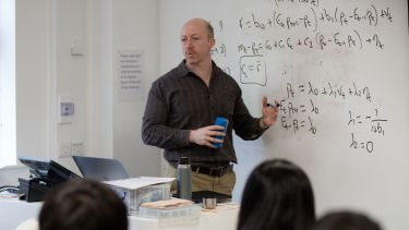 An academic member of staff delivering a seminar and using a whiteboard - image