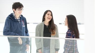 Three students laughing together - image