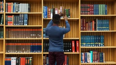 a student is taking a book off a sheld in Western Bank Library