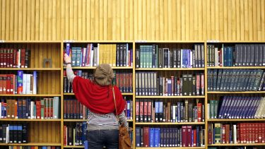 Woman choosing a book from the library