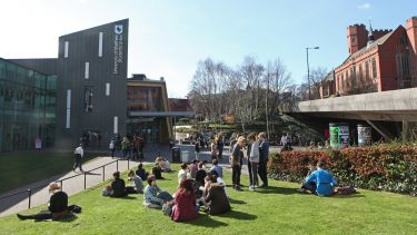 A group of students sat outside of the Students' Union building.