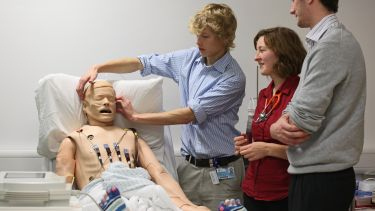 A group of medical students observing a demonstration on a dummy.
