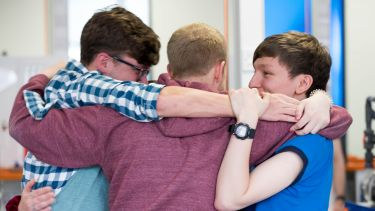 An image of three students in a group hug