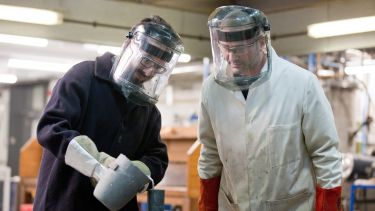 An image of student and supervisor in protective clothing in a materials engineering lab