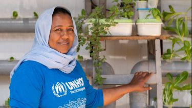 Syrian refugee with hydroponics-grown plants in the Zaatari refugee camp in Jordan