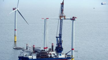 Offshore wind turbine at sea having a blade installed.