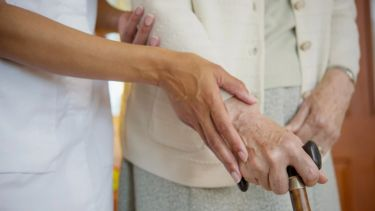 A medical practitioner assists an elderly person who is using a walking stick