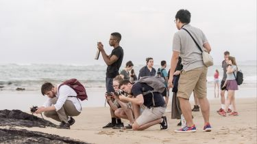 Students take photos on Galapagos beach to investigate coastal processes