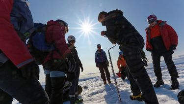 Researchers drill into ice while the sun beats down on them