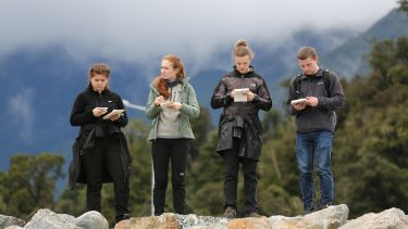 Four students study their notes during fieldwork in New Zealand