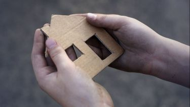 cardboard house in two hands