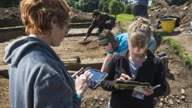 Archaeology students at a dig site use tablets to enter their findings.