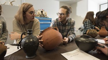Two archaeology students examine ancient pots in a seminar.