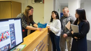 Three students getting assistance from a member of staff at the Students at the Student Experience Office