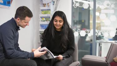 Two students reading a brochure in the employability hub