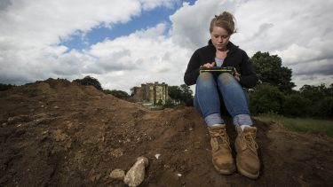 A student wearing outerwear and hiking boots sits by an excavation site using a tablet.