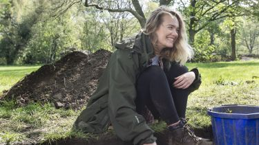 An archaeology student sat by an excavation site in a wooded area.