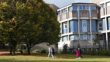 Some students walking on a grassy path with the Geography building in the background behind them.