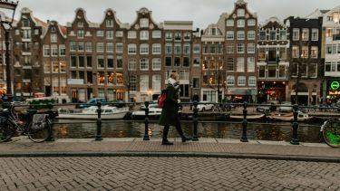 Woman walking alongside canal in Amsterdam