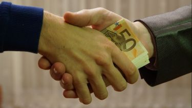 Money being transferred during a handshake